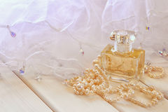Dreamy photo of white pearls necklace and perfume bottle Royalty Free Stock Image
