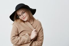 Dreamy pleased positive young female in retro coat and hat, wearing stylish eyeglasses, wraps in coat, stands against. Gray background, looks at camera with Royalty Free Stock Images