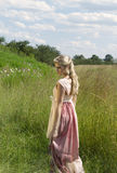 Dreamy portrait of bohemian blonde girl in field of grass Royalty Free Stock Photo