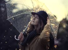 Dreamy portrait with bokeh glitter. Young woman dreamy mood under rain with illuminated transparent umbrella. Wearing wool coat and stylish hat Royalty Free Stock Photos