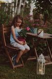 Dreamy romantic kid girl relaxing in evening summer garden. Decorated with lantern and candle holder lights Royalty Free Stock Photography