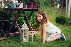 Dreamy romantic kid girl relaxing in evening summer garden decorated with lantern. And candle holder lights Royalty Free Stock Images