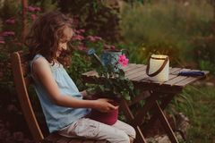 Dreamy romantic kid girl relaxing in evening summer garden. Decorated with lantern and candle holder lights Stock Photo