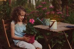 Dreamy romantic kid girl relaxing in evening summer garden. Decorated with lantern and candle holder lights Stock Photography