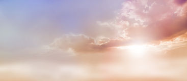 Dreamy Romantic Sky scape. Beautiful wide peach and dusky pale blue sky and cloud scape with a burst of sunlight emerging from under the cloud base with plenty Royalty Free Stock Photography