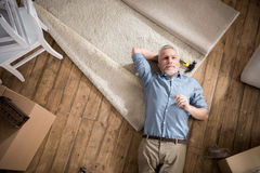 Dreamy senior man looking away while lying on floor Royalty Free Stock Photos