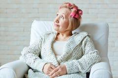 Dreamy senior woman on armchair Royalty Free Stock Photography