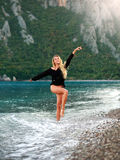 Dreamy sensual woman enjoys nature of sea in water splashes Stock Images
