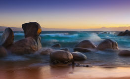 Dreamy Shorline Waves. Dreamy Sunset shot of sandy beach with large rocks and waves Royalty Free Stock Photo