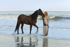 Dreamy shot of woman with horse in the ocean Stock Photos