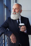 Dreamy sir holding coffee and looking out window Royalty Free Stock Photo