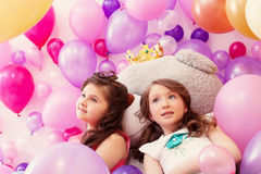 Dreamy sisters posing lying on big teddy bear Stock Images