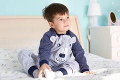 Dreamy small kid with dark hair, pleasant apperance, wears soft pyjamas, sits on comfortbale bed in his room, looks thoughtfully a. Way, dreams about new toy or Royalty Free Stock Photos
