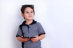 Dreamy smiling cute boy with smartphone in hands. Technology, mo. Bile apps, children and parental advisory, lifestyle concept Royalty Free Stock Photo