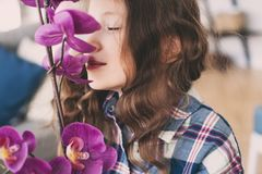 Dreamy smiling kid girl smells orchid flower. At home royalty free stock images