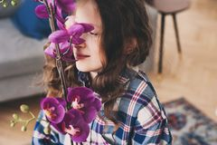 Smiling kid girl smells orchid flower at home. Dreamy smiling kid girl smells orchid flower at home royalty free stock photos