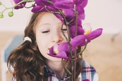 Smiling kid girl smells orchid flower at home. Dreamy smiling kid girl smells orchid flower at home stock image