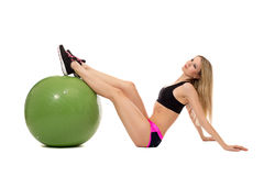 Dreamy sporty girl threw her feet on fitness ball Royalty Free Stock Photo