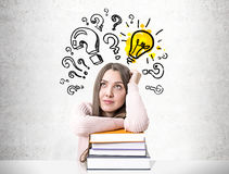 Dreamy student with a pile of books, bulb question Stock Image