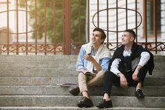 Dreamy students on break outside. Two happy men background, street hipster style, young males outdoors Stock Photo