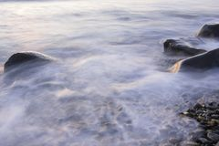 Dreamy surf flowing over rocky shore royalty free stock images