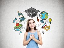Dreamy teen girl in blue, education icons. Portrait of a dreamy teen girl wearing a blue dress and standing near a concrete wall with education icons on it royalty free stock images