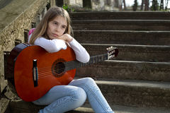 Dreamy Teenage Girl Holding a Guitar in Her Lap and Looking Away Stock Photos