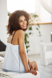 Dreamy tender african girl in sleepwear sitting on bed in morning smiling thinking. Copy space. Young dreamy tender african girl in sleepwear sitting on bed in Stock Photography