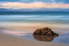 Dreamy waves breaking in slow motion at Plettenberg Bay beach at sunset, with hills in the distance and a rock in the foreground. Reflected in the water. Garden royalty free stock photos