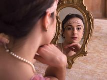 Dreamy woman in 1920s headband with mirror stock image
