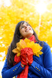 Dreamy woman on autumn sunshine day. Happy woman having fun with leaves on autumn sunshine day in park. Beautiful girl smiling and looking up towards copy space Royalty Free Stock Images