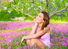 Dreamy woman in blooming park. Dreamy woman spending time in blooming park, enjoying first blossom of nature, happy weekend in countryside, relaxation outdoors Royalty Free Stock Photos