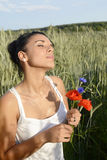 Dreamy woman with bouquet. Dreamy young  woman with bouquet in cornfield Stock Photo