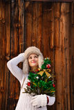 Dreamy woman with Christmas tree in front of rustic wood wall Royalty Free Stock Image