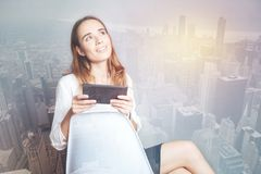 Dreamy woman with a gadget sitting on a white chair Royalty Free Stock Photo