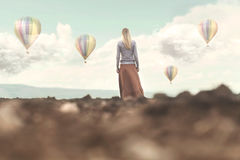 Dreamy woman looking at the hot air balloons coming down Royalty Free Stock Photos
