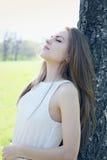 Dreamy woman near the tree. Dreamy beautiful young woman near the tree Stock Photo