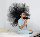 Dreamy woman in a nightgown praying on the bed. With her hair flying around her head. Expressive prayer of girl in bed. Fervent meditation at home Royalty Free Stock Photo
