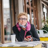 Dreamy woman with phone in cafe. Dreamy woman sitting in outside cafe with coffee and smartphone and looking at camera Royalty Free Stock Images