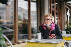 Dreamy woman with phone in cafe. Dreamy woman sitting in outside cafe with coffee and smartphone and looking at camera Stock Photography