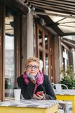 Dreamy woman with phone in cafe. Dreamy woman sitting in outside cafe with coffee and smartphone and looking at camera Royalty Free Stock Image