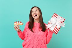 Dreamy woman in pink sweater looking up, hold eclair cake, red striped present box with gift ribbon isolated on blue. Background. Valentine`s, Women`s Day royalty free stock photography