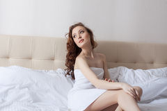 Dreamy woman posing in hotel bedroom Stock Images
