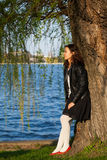 Dreamy woman. Profile of a serene dreamy woman standing near a tree in a park and looking away Royalty Free Stock Photos