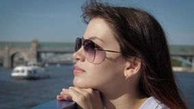 Dreamy woman put her head to handrail looking view from a boat on promenade. Close up side view, portrait of dreamy caucasian attractive woman with sunglasses stock video footage