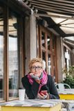 Dreamy woman with phone in cafe. Dreamy woman sitting in outside cafe with coffee and smartphone and looking at camera Royalty Free Stock Photos