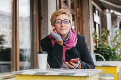 Dreamy woman with phone in cafe. Dreamy woman sitting in outside cafe with coffee and smartphone and looking at camera Stock Photos