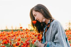 Dreamy woman smelling a poppy flower in meadow. Dreamy attractive brunette young woman smelling a red poppy in flower meadow, summer vacations stock image