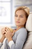 Dreamy woman with tea mug. Portrait of dreamy attractive woman holding tea mug, thinking Stock Photo