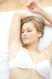 Dreamy woman in underwear lying on bed Stock Photos